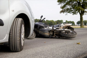 A car in front of a wrecked motorcycle